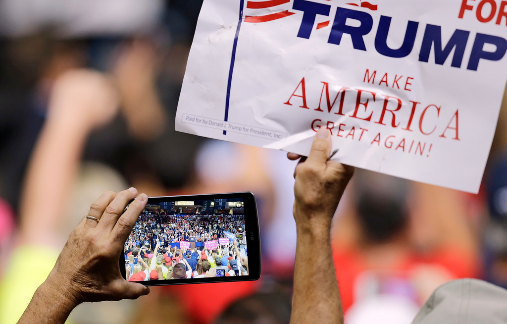 . A supporter holds up a sign and records on his phone as President Donald Trump speaks at the Covelli Centre, Tuesday, July 25, 2017, in Youngstown, Ohio. (AP Photo/Tony Dejak)