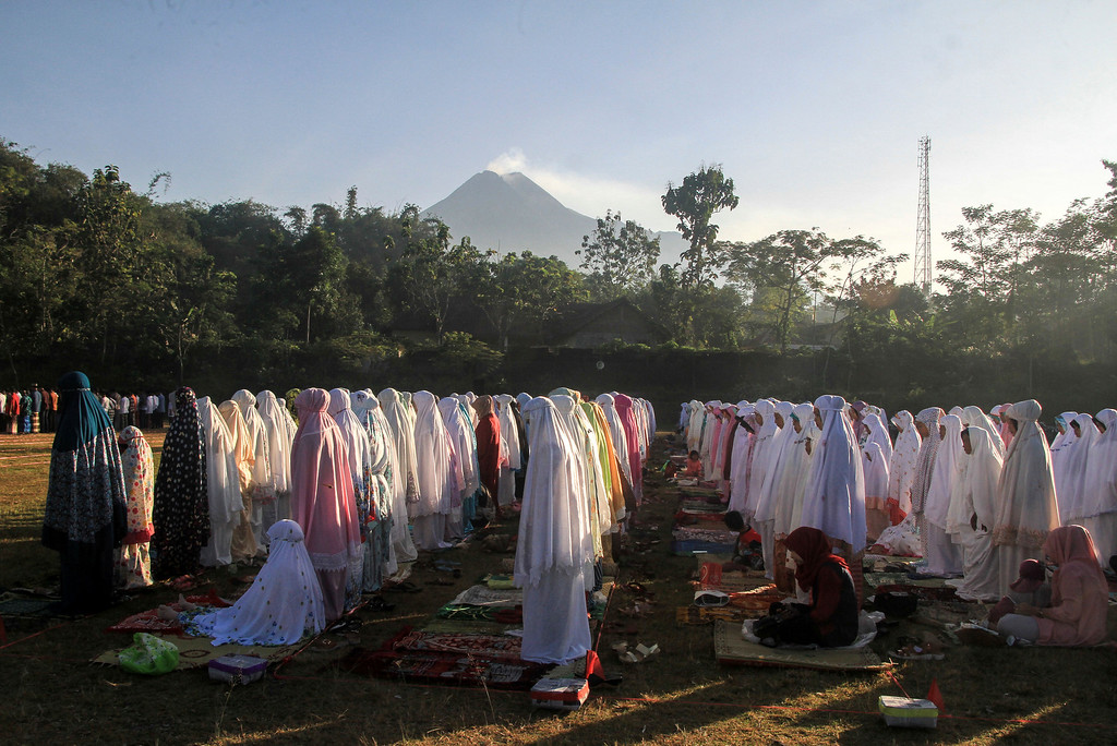 . Indonesian Muslims offer Eid al-Fitr prayers to mark the end of the holy fasting month of Ramadan as Mount Merapi is seen in the background at Sleman, Yogyakarta, Indonesia, Friday, June 15, 2018. (AP Photo/Slamet Riyadi)