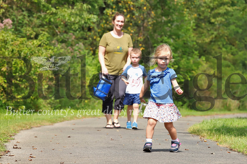 Emily, 2, P.J. and Tricia Rolsma of Cranberry enjoy a sunny walk Wednesday in the community park at Seven Fields in Mars. 07/31/19 Seb Foltz/Butler Eagle