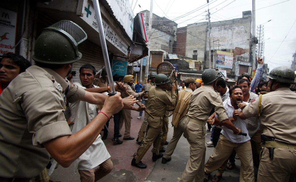 . An Indian policeman beats a Hindu protestor protesting against the state government after rival communities clashed in Kishtwar, in Jammu, India, Saturday, Aug. 10, 2013. Indian forces fired warning shots Saturday to enforce a curfew and to push angry people back into their homes in Kishtwar, in the Indian portion of Kashmir where clashes between Muslims and Hindus during Eid celebrations killed at least two people and injured another 24.(AP Photo/Channi Anand)