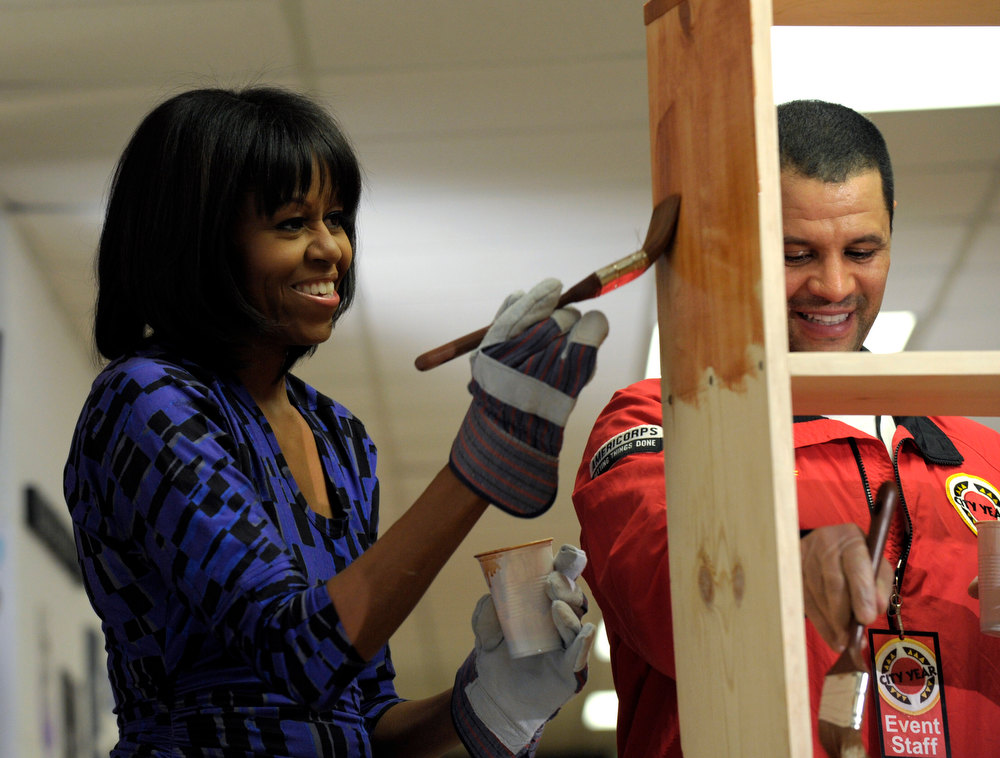 Description of . First lady Michelle Obama, accompanied by Jeff Franco, executive director of City Year, stains a bookshelf at Burrville Elementary School in Washington, Saturday, Jan. 19, 2013, as the first family participated in a community service project for the National Day of Service, part of the 57th Presidential Inauguration. (AP Photo/Susan Walsh)