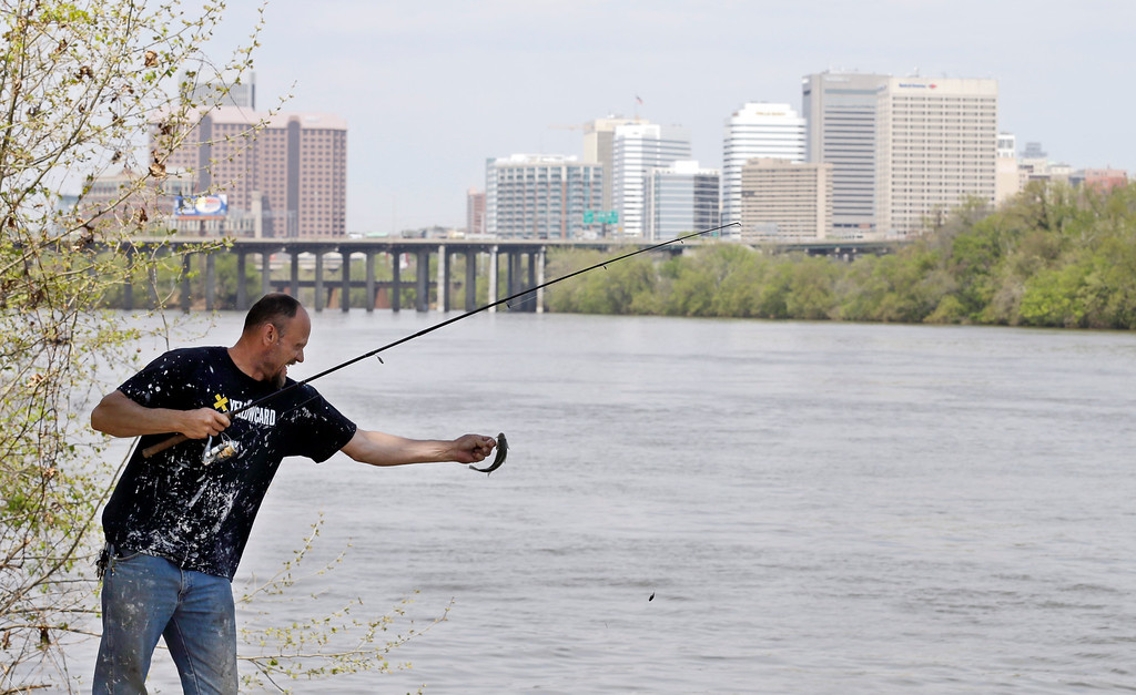 . A fisherman releases his catch along the James River near downtown Richmond, Va., Tuesday, April 22, 2014. (AP Photo/Steve Helber)