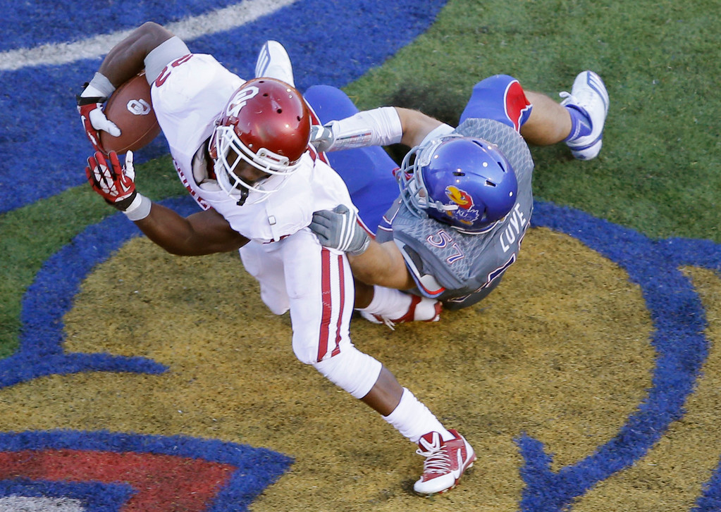 . Oklahoma running back Roy Finch (22) breaks a tackle by Kansas linebacker Jake Love, right, during the second half of an NCAA college football game in Lawrence, Kan., Saturday, Oct. 19, 2013. Oklahoma defeated Kansas 34-19. (AP Photo/Orlin Wagner)