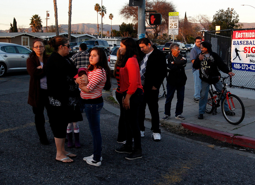 . People stand at the corner of Bermuda Way and Ocala Ave. as San Jose Police Officers investigate a double homicide at a home on the 1800 block of Bermuda Way in San Jose, Calif., on Thursday, Feb. 14, 2013.  (Nhat V. Meyer/Staff)