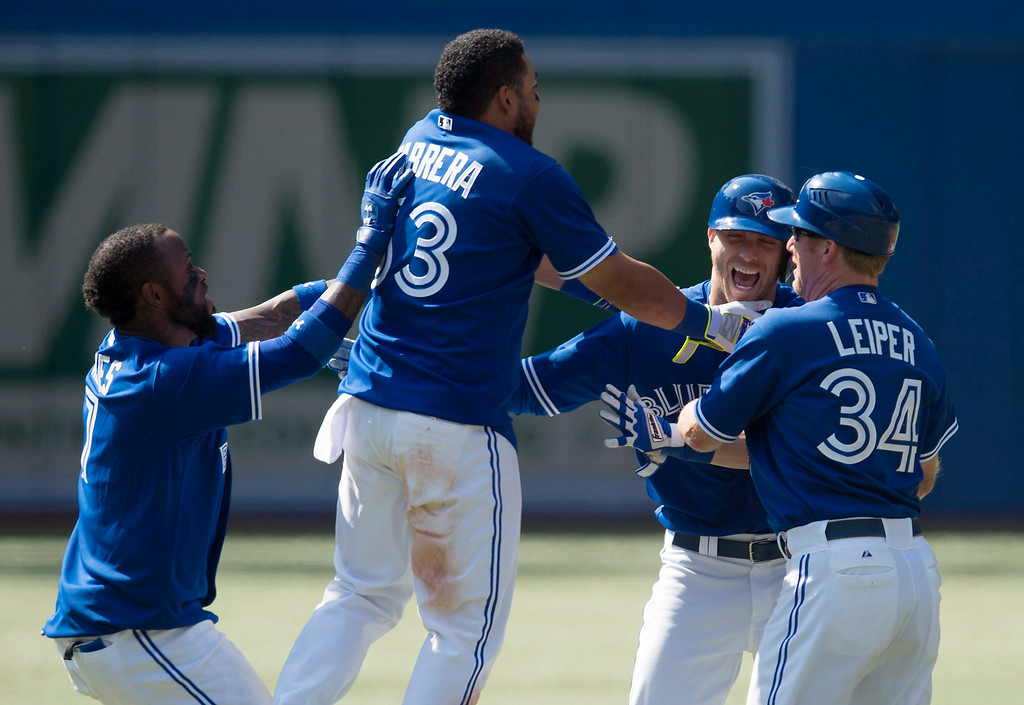 . Toronto Blue Jays\' Nolan Reimold, second from right, is mobbed by, from left to right, Jose Reyes, Melky Cabrera, and Tim Leiper following Reimold\'s game-winning RBI double in the tenth inning of a baseball game, Saturday, Aug. 9, 2014 in Toronto. The Blue Jays defeated the Tigers 3-2. (AP Photo/The Canadian Press, Darren Calabrese)
