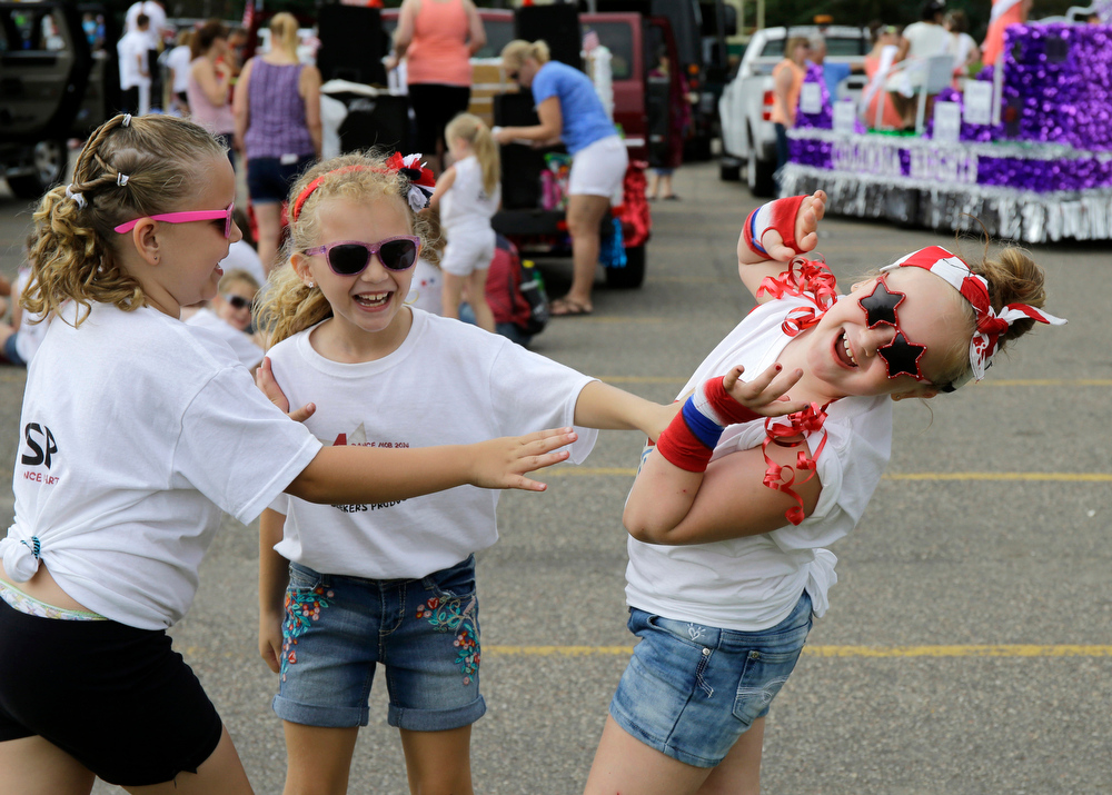 Description of . Seven-year-old Charlie Pedersen, right, plays red light/green light with dance studio friends before participating in the in the Delano Fourth of July parade in Delano, Minn., Friday, July 4, 2014.  (AP Photo/Ann Heisenfelt)