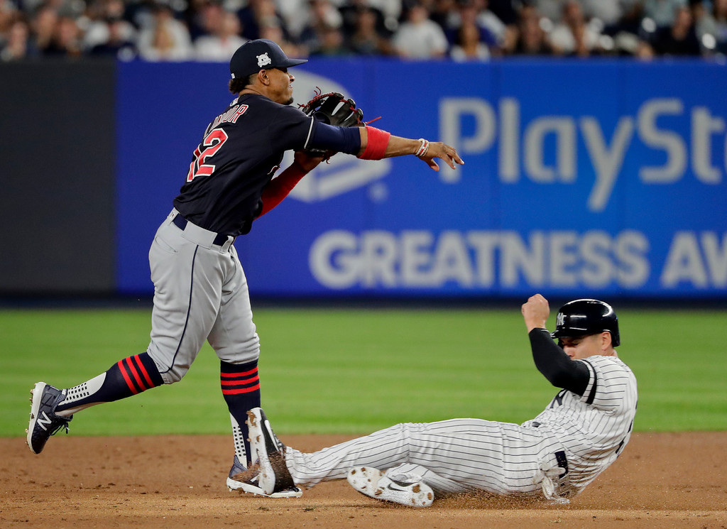 . New York Yankees\' Jacoby Ellsbury tries to break up the double play as Cleveland Indians shortstop Francisco Lindor (12) makes the throw to first during the third inning in Game 3 of baseball\'s American League Division Series, Sunday, Oct. 8, 2017, in New York. Ellsbury was out at second and Aaron Hicks was out at first. (AP Photo/Frank Franklin II)