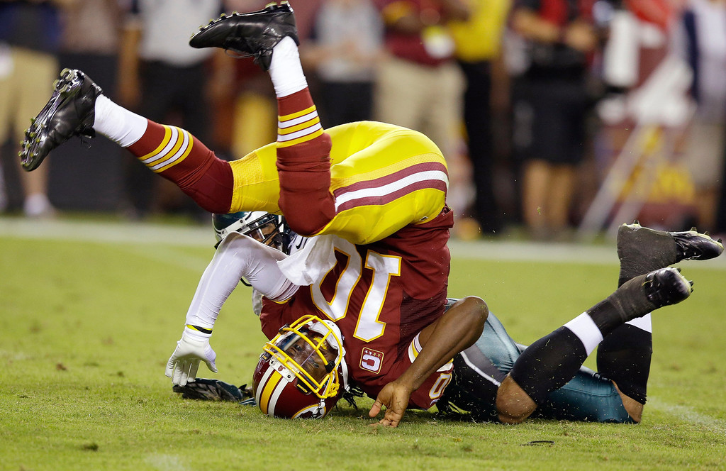. Washington Redskins quarterback Robert Griffin III rolls onto his head after he is tackled by Philadelphia Eagles outside linebacker Mychal Kendricks during the first half of an NFL football game in Landover, Md., Monday, Sept. 9, 2013. (AP Photo/Alex Brandon)