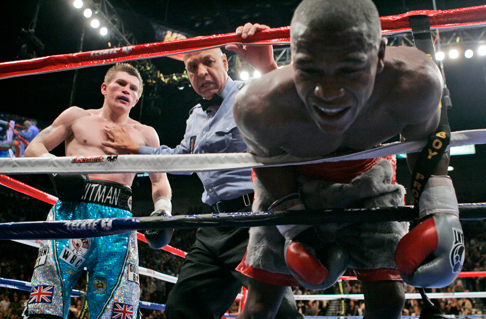 . Ricky Hatton, of Great Britain, left, is held back from referee Joe Cortez after being called for hitting Floyd Mayweather Jr. in the back of the head during their WBC welterweight boxing title fight at the MGM Grand hotel-casino in Las Vegas, Saturday, Dec. 8, 2007. (AP Photo/Jae C. Hong)