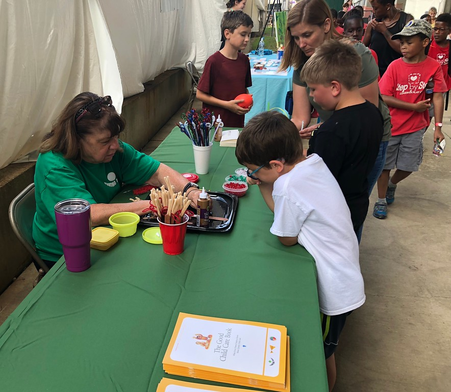 . Tawana Roberts � The News-Herald <br> Starting Point Lake County Outreach Coordinator Cathy Zeller assists kids with crafts at the 2018 Lake County Fair on July 26.