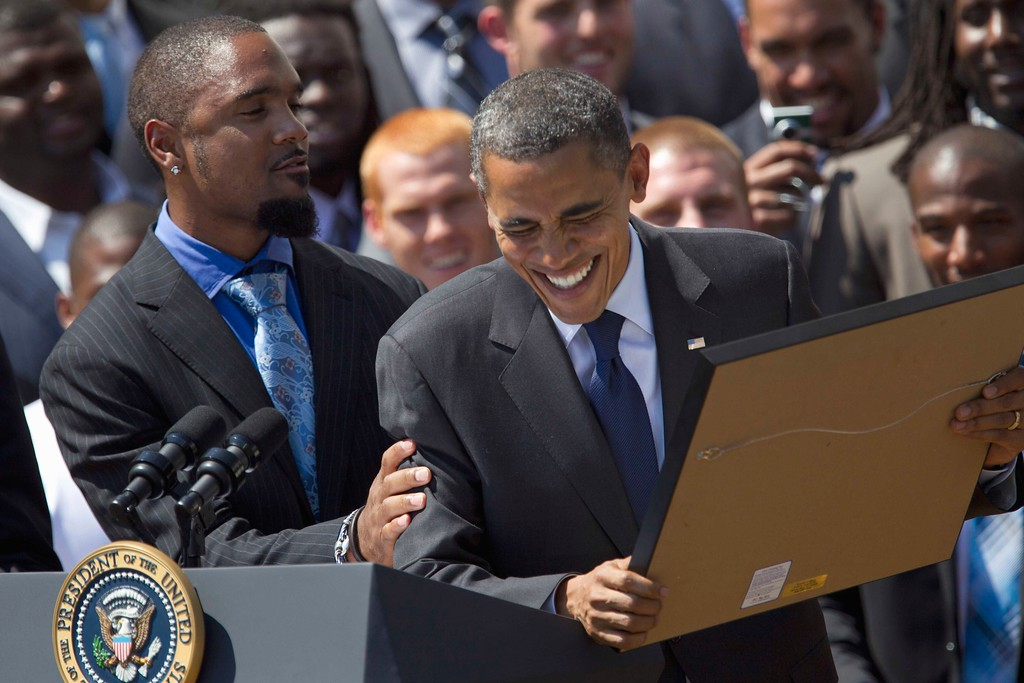. President Barack Obama reacts to be presented a stock certificate by Green Bay Packers football cornerback Charles Woodson, left, during a ceremony honoring the Super Bowl XLV Champion Green Bay Packers, Friday, Aug. 12, 2011, on the South Lawn of the White House in Washington. On the far right is team General Manager Ted Thompson.  (AP Photo/Carolyn Kaster)