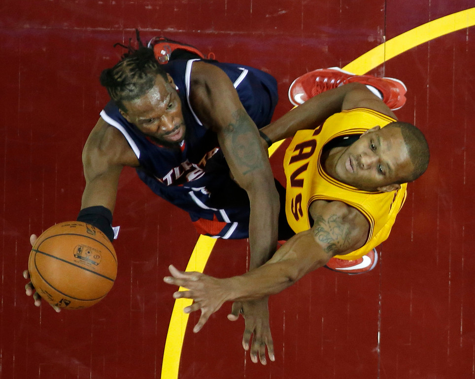 . Atlanta Hawks\' DeMarre Carroll, left, shoots over Cleveland Cavaliers\' James Jones during the first half in Game 3 of the Eastern Conference finals of the NBA basketball playoffs Sunday, May 24, 2015, in Cleveland. (AP Photo/Tony Dejak)