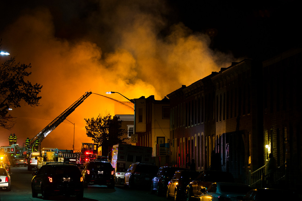 . Firefighters battle a blaze, Monday, April 27, 2015, after rioters plunged part of Baltimore into chaos, torching a pharmacy, setting police cars ablaze and throwing bricks at officers. (AP Photo/Evan Vucci)