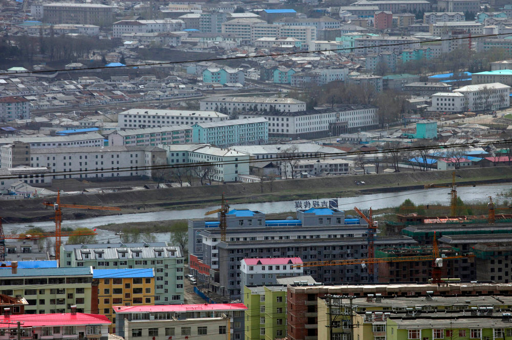 . The North Korean city of Hyesan (top), is seen across the Yalu River from the Chinese town of Changbai in this general view taken May 12, 2013. Chinese currency and U.S. dollars are being used more widely than ever in North Korea instead of the country\'s own money. The use of dollars and Chinese yuan, or renminbi, has accelerated since a revaluation of the North Korean won in 2009 wiped out the savings of millions of people, said experts on the country, defectors and Chinese border traders.  REUTERS/John Ruwitch