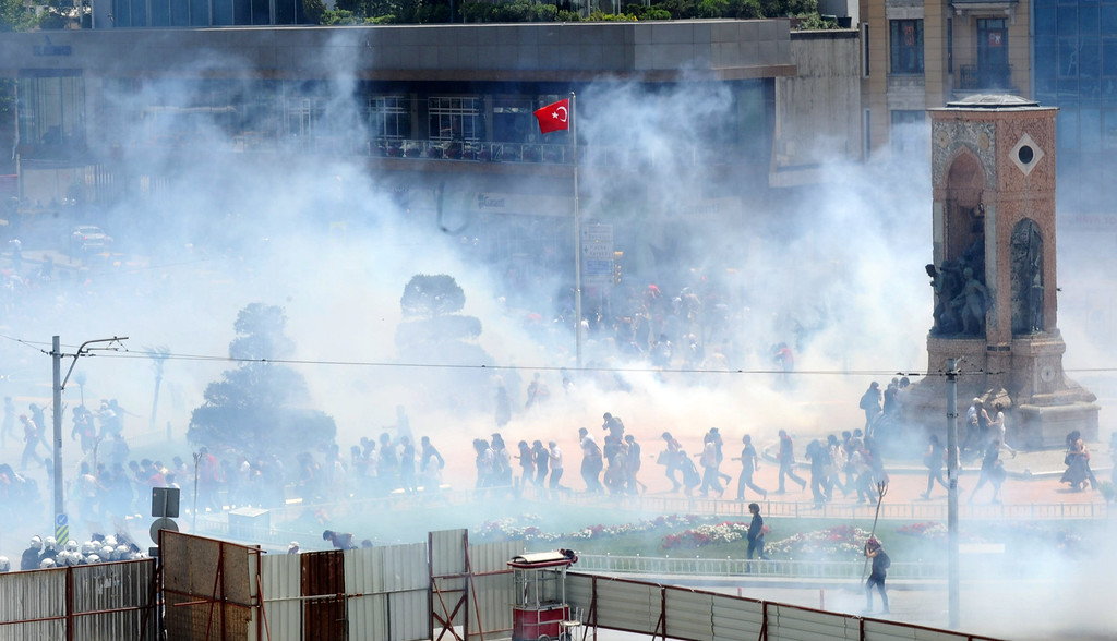 . Demonstrators help one another as Turkish riot policemen use tear gas to disperse clashes on May 31, 2013 during a protest against the demolition of Taksim Gezi Park, in Taksim Square in Istanbul. Police reportedly used tear gas to disperse a group, who were standing guard in Gezi Parki to prevent the Istanbul Metropolitan Municipality from demolishing the last remaining green public space in the center of Istanbul as a part of a major Taksim renewal project. At least a dozen people were injured. BULENT KILIC/AFP/Getty Images
