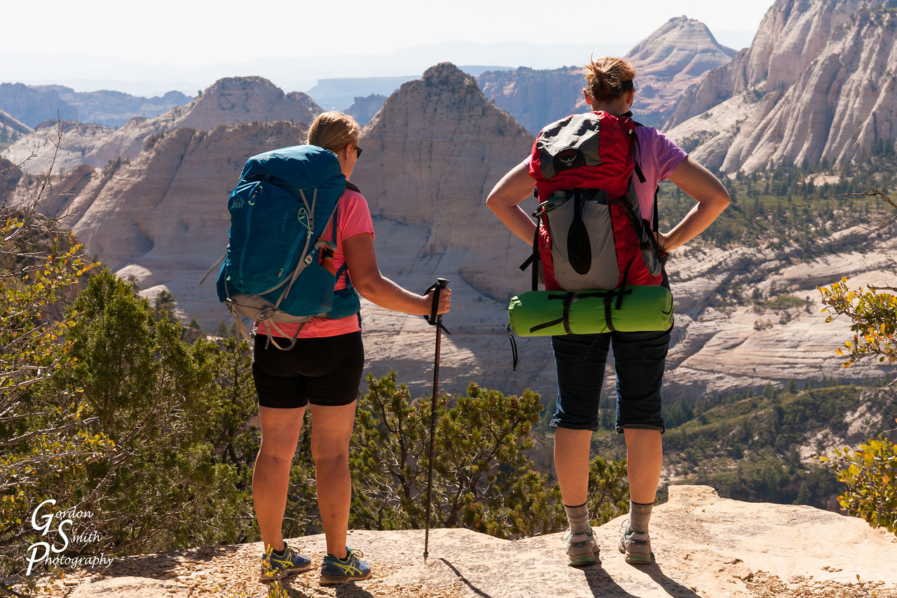 Women backpack high over cliffs in Zion, Utah
