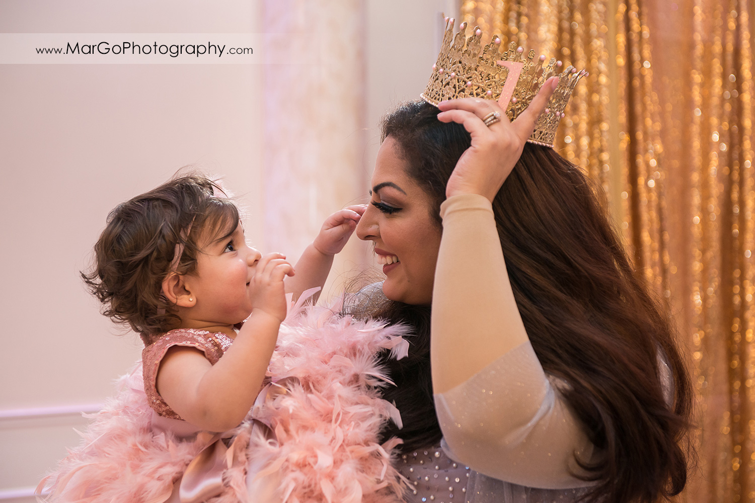 birthday girl in pink feather dress taking gold crown from her mom at Newark Oasis Palace
