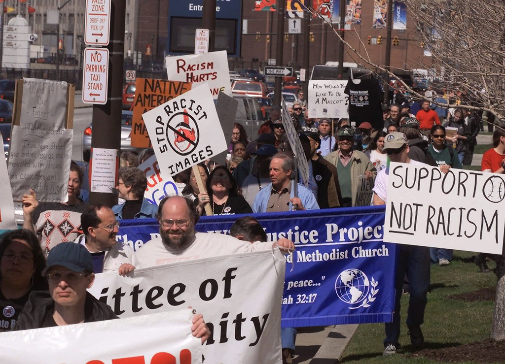 . A group of about 60 people march around Jacobs Field in Cleveland to protest the Cleveland Indians Chief Wahoo logo before the team\'s home opener Friday, April 14, 2000. (AP Photo/Mark Duncan).