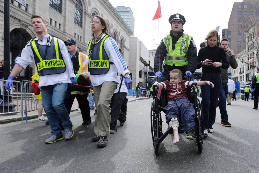 . A Boston police officer wheels in injured boy down Boylston Street as medical workers carry an injured runner following an explosion during the 2013 Boston Marathon in Boston, Monday, April 15, 2013. Two explosions shattered the euphoria at the marathon\'s finish line on Monday, sending authorities out on the course to carry off the injured while the stragglers were rerouted away from the smoking site of the blasts. (AP Photo/Charles Krupa)