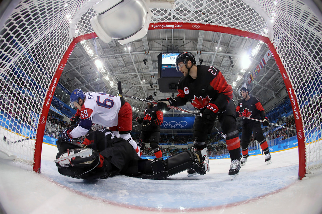 . Lukas Radil (69), of the Czech Republic, falls on goal eBen Scrivens (30), of Canada, as they battle for the puck during the first period of the preliminary round of the men\'s hockey game at the 2018 Winter Olympics in Gangneung, South Korea, Saturday, Feb. 17, 2018. (Bruce Bennett/Pool Photo via AP)