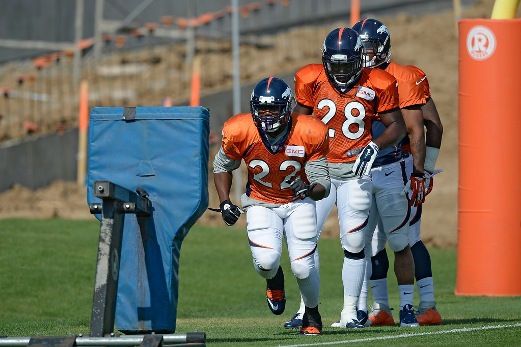 . Denver Broncos running back C.J. Anderson (22) hits the sled during drills on day five of the Denver Broncos 2014 training camp July 28, 2014 at Dove Valley. (Photo by John Leyba/The Denver Post)