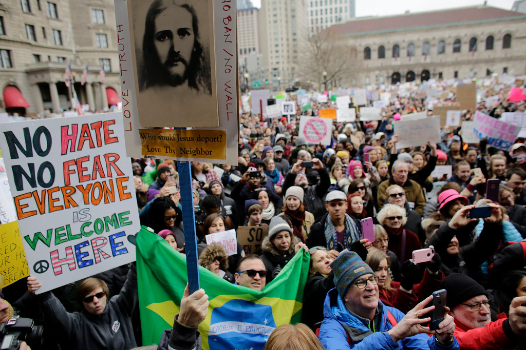 . Demonstrators display placards during a rally against President Donald Trump\'s order that restricts travel to the U.S., Sunday, Jan. 29, 2017, in Boston. Trump signed an executive order Friday, Jan. 27, 2017 that bans legal U.S. residents and visa-holders from seven Muslim-majority nations from entering the U.S. for 90 days and puts an indefinite hold on a program resettling Syrian refugees. (AP Photo/Steven Senne)