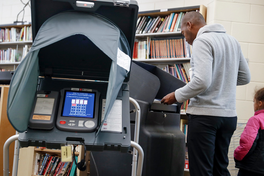 . A voter casts his ballot into an electronic voting machine at a polling station located in the Taft Information Technology High School, Tuesday, Nov. 7, 2017, in Cincinnati. Ohio voters will decide ballot issues on Tuesday that would place limits on drug prices and expand victims\' rights in criminal proceedings, along with several mayoral races. (AP Photo/John Minchillo)