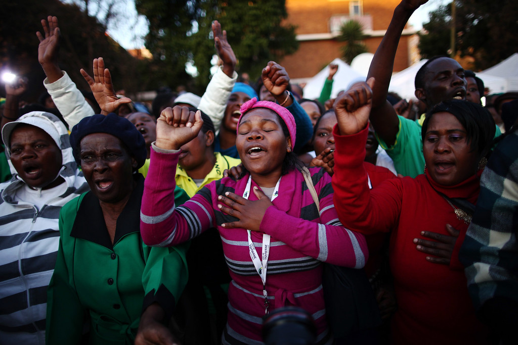 . PRETORIA, SOUTH AFRICA - JUNE 27:  Supporters of former South African President Nelson Mandela gather as they wait to hear news of his condition outside the Heart Hospital where Mandela is being treated for a lung infection June 27, 2013 in Pretoria, South Africa. Family members and President Jacob Zuma visited Mandela during his 20th day in the hospital.  (Photo by Dan Kitwood/Getty Images)