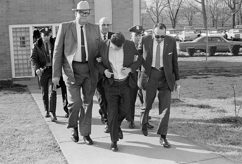 . James Earl Ray lowers his head as State Safety Commissioner Greg O\'Rear, white hat, and Highway Patrol Maj. Mickey McGuire, dark glasses, lead him to prison in Nashville, Tenn., March 11, 1969.  Ray is serving a 99-year sentence in the death of Dr. Martin Luther King Jr. in Memphis. (AP Photo)