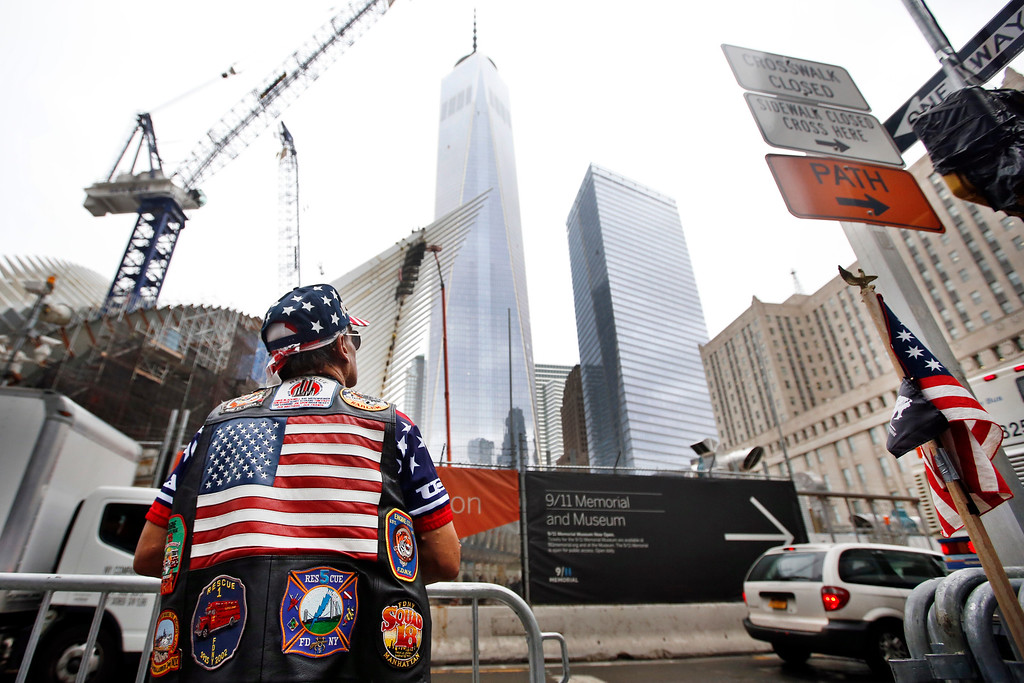 . Jose Colon, of New York, looks up at 1 World Trade Center before a ceremony marking the 13th anniversary of the Sept. 11, 2001 attacks, Thursday, Sept. 11, 2014, in New York. (AP Photo/Jason DeCrow)