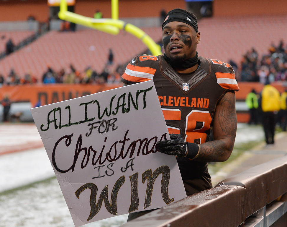 . Cleveland Browns inside linebacker Christian Kirksey holds a sign after the Browns lost to the Cincinnati Bengals  in an NFL football game, Sunday, Dec. 11, 2016, in Cleveland. (AP Photo/David Richard)