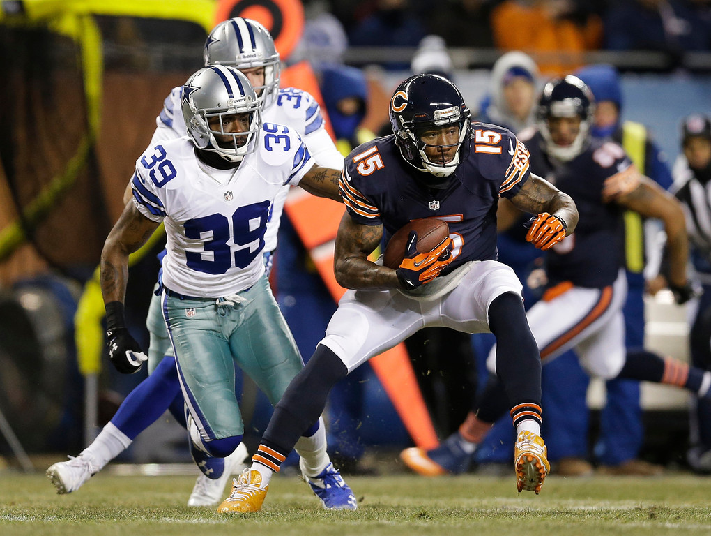 . Chicago Bears wide receiver Brandon Marshall (15) runs past Dallas Cowboys cornerback Brandon Carr (39) after making a catch during the first half of an NFL football game, Monday, Dec. 9, 2013, in Chicago. (AP Photo/Nam Y. Huh)