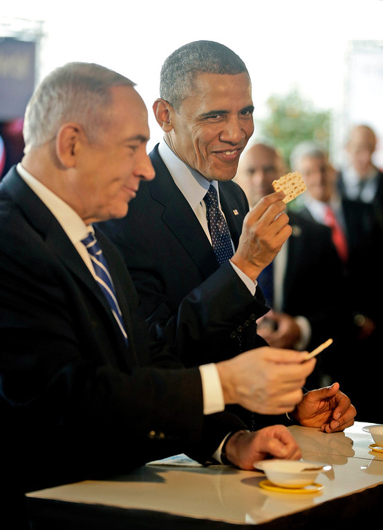 . U.S. President Barack Obama, right, and Israeli Prime Minister Benjamin Netanyahu take a bite of matzah as they tour the Technology Expo in Jerusalem, Israel,Thursday, March 21, 2013. (AP Photo/Pablo Martinez Monsivais)