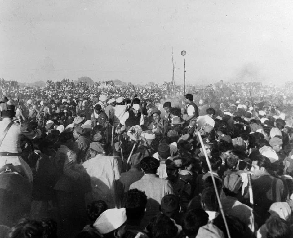 . Crowds rushing towards the funeral pyre of the assassinated Indian statesman and advocate of non-violence, Mahatma Gandhi (Mohandas Karamchand Gandhi), before the fire is lit, 12th February 1948.  (Photo by Devi/Fox Photos/Getty Images)