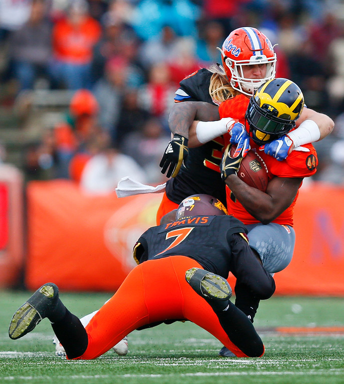 . South squad safety Damarius Travis of Minnesota (7) and South squad inside linebacker Alex Anzalone of Florida (34) tackle North squad running back De\'Veon Smith of Michigan (44) during the first half of the Senior Bowl NCAA college football game, Saturday, Jan. 28, 2017, at Ladd�Peebles Stadium, in Mobile, Ala. (AP Photo/Brynn Anderson)