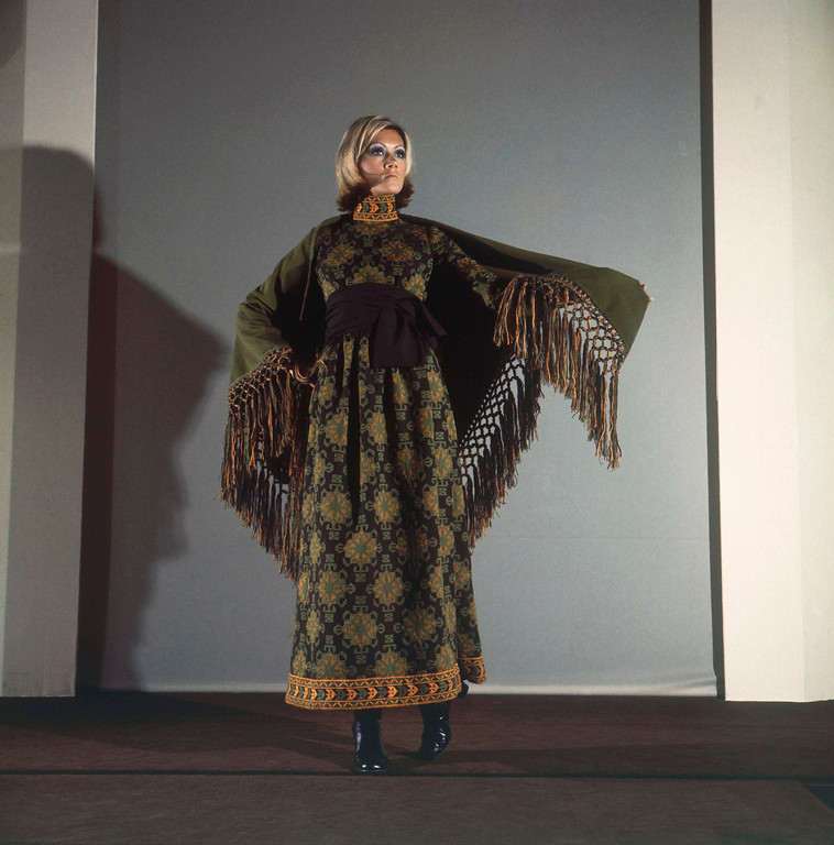 . A long brown cocktail dress with green and yellow embroideries wore with a green woolen crepe shawl and black leather boots, August 10, 1970. From the autumn /winter collection of Guy La Roche of Paris. (AP Photo/Marqueton)