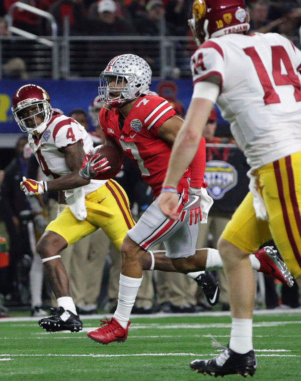 . Ohio State safety Damon Webb (7) runs for a touchdown after an interception as Southern California quarterback Sam Darnold (14) and wide receiver Steven Mitchell Jr. (4) chase him during the first half of the Cotton Bowl NCAA college football game in Arlington, Texas, Friday, Dec. 29, 2017. (AP Photo/LM Otero)