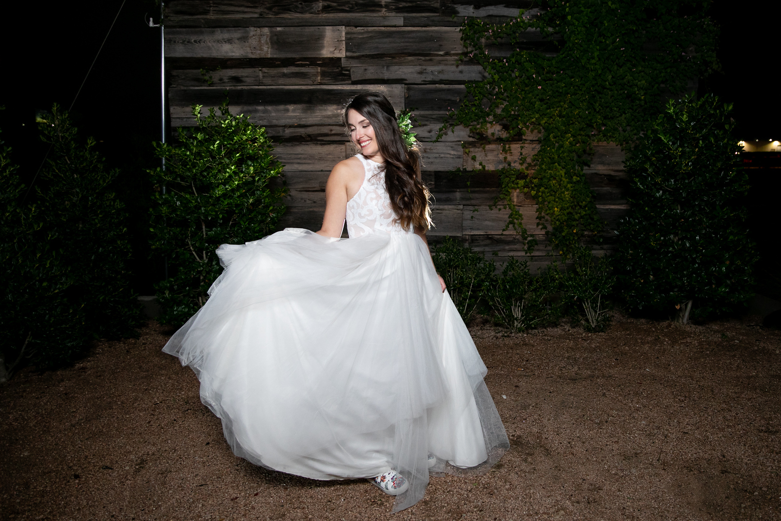 a bride walking through a gravel lot smiling as she looks down at her flowing princess style wedding gown