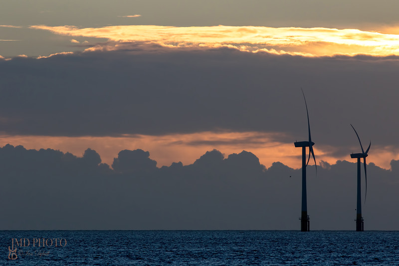 Offshore wind farm turbines silhouette at sunrise or sunset.