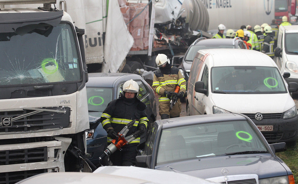 . Firefighters carry heavy equipment at the scene of a crash on the A19 highway in Zonnebeke, western Belgium, Tuesday, Dec. 3, 2013. (AP Photo/Yves Logghe)