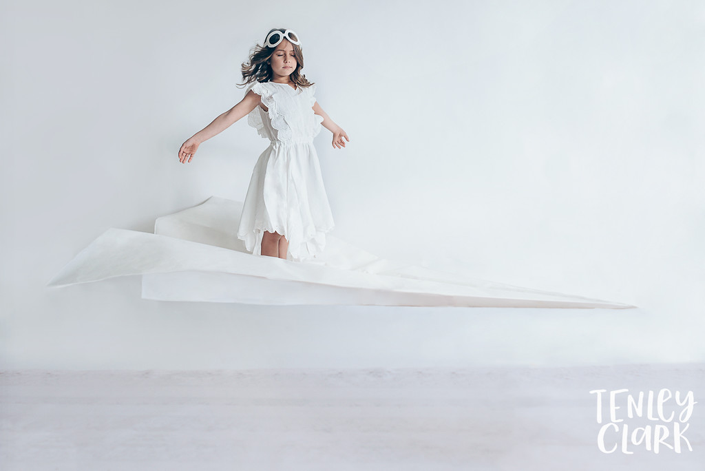 Girl flying on a paper airplane. Whimsical kid's fashion editorial with giant white paper origami props. Photography by Tenley Clark.