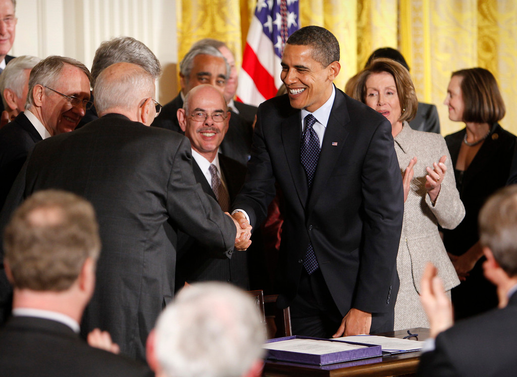 . President Barack Obama shakes hands with Rep. John Dingell, D-Mich., after signing into law the State Children\'s Health Insurance Program (SCHIP) in the East Room of the White House in Washington, Wednesday, Feb. 4, 2009. Pictured from left: Senate Majority Leader Harry Reid, D-Nev., Rep. Henry Waxman, D-Calif. and House Speaker Nancy Pelosi. (AP Photo/Lawrence Jackson)