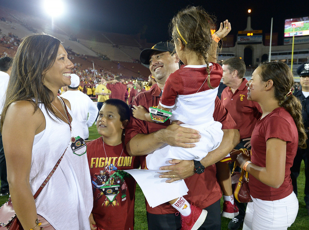 . USC Coach Steve Sarkisian gets love from his family after the game. Wife Stephanie, son Bradley,9, daughters Taylor,6, and Ashley, 12 all rushed onto the field to give him hugs and kisses. It was the first game for the new coach. USC defeated Fresno State 52-13 at the Los Angeles Memorial Coliseum. Los Angeles, CA. 8/30/2014(Photo by John McCoy Daily News
