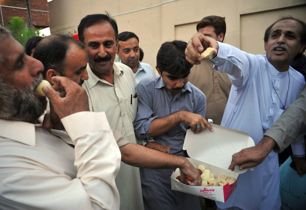""". Pakistani NGO activists eat sweets as they celebrate after news that Malala Yousafzai won the Nobel Peace Prize, in Peshawar on October 10, 2014. Malala Yousafzai was hailed as the \""""pride of Pakistan\"""" by Prime Minister Nawaz Sharif on Friday for winning the Nobel Peace Prize, as a former fellow pupil said the award was a victory for every girl in the country. Political leaders and activists alike rallied around Malala, the youngest ever Nobel laureate, expressing their support for the education campaigner who moved to Great Britain after being shot in the head by Taliban militants two years ago. AFP PHOTO/ HASHAM  AHMED/AFP/Getty Images"""