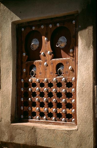 mud house has wooden window shutters