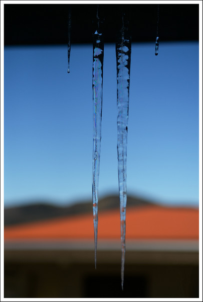 Icicles dripping from the vent in front of our door.  The orange is the roof of the adjacent apartment.