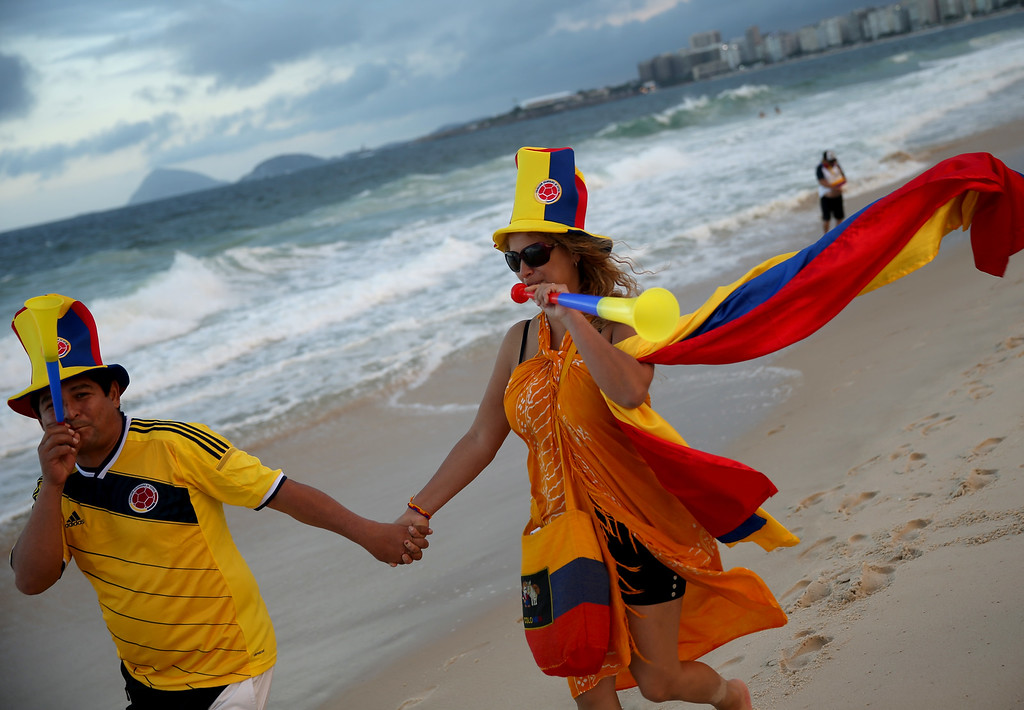 . Colombian soccer team fans, Pedro Caicedo Ramirez (L) and Isabel Maldonado, from Colombia, enjoy Copacabana beach while waiting for the start of the 2014 FIFA World Cup on June 11, 2014 in Rio de Janeiro, Brazil.   Brazil continues to prepare to host the World Cup which starts on June 12th and runs through July 13th.  (Photo by Joe Raedle/Getty Images)