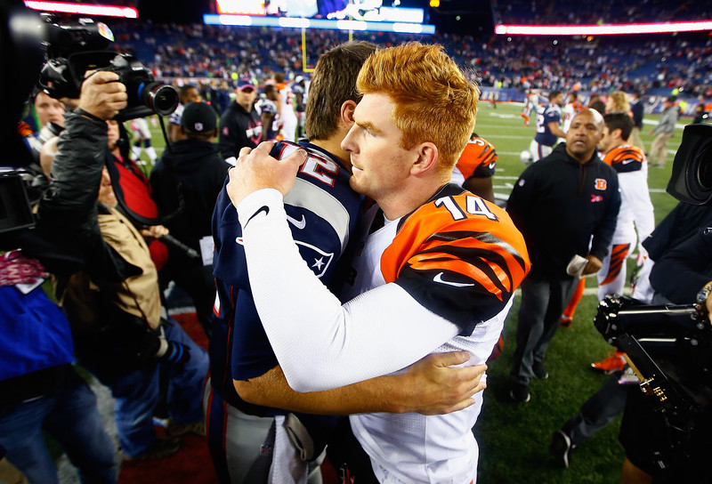 . Tom Brady #12 of the New England Patriots and Andy Dalton #14 of the Cincinnati Bengals hug after the game at Gillette Stadium on October 5, 2014 in Foxboro, Massachusetts.  (Photo by Jared Wickerham/Getty Images)