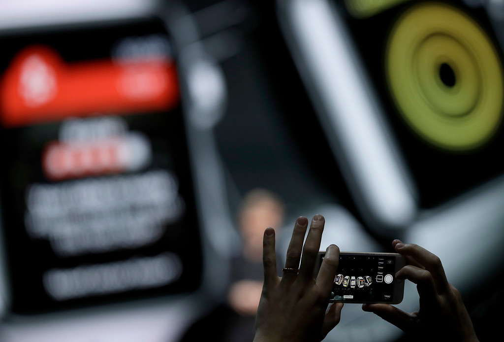 . An attendee takes a photo as Kevin Lynch, Apple\'s vice president of technology, speaks about the Apple Watch during an announcement of new products at the Apple Worldwide Developers Conference Monday, June 4, 2018, in San Jose, Calif. (AP Photo/Marcio Jose Sanchez)