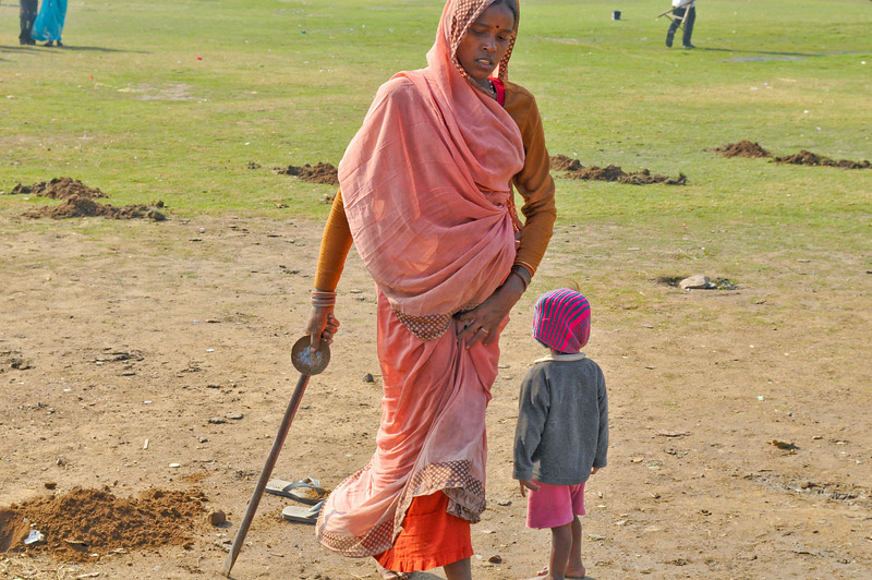 This woman was digging holes for a fence to be put in place for India Day in late January. Her child accompanied her.